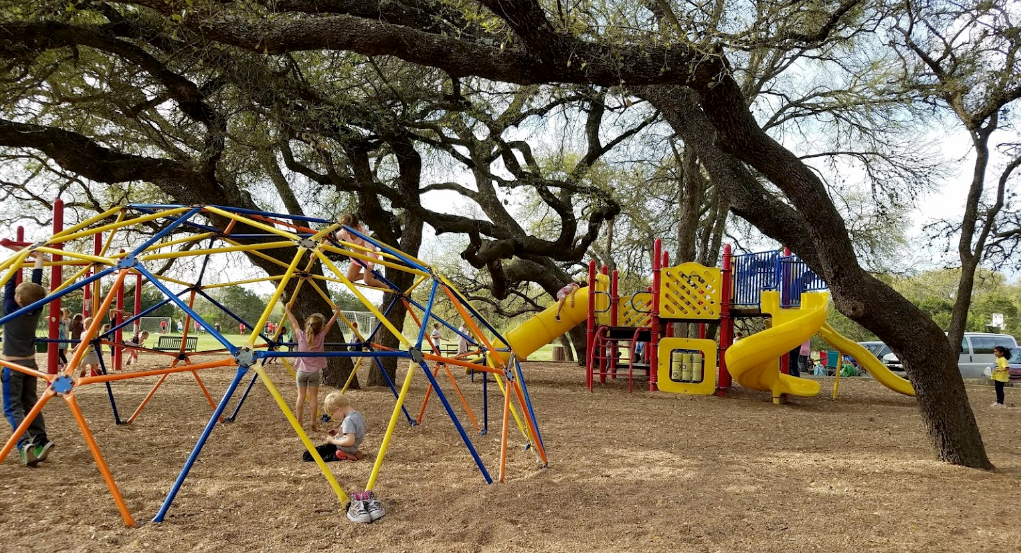 Large blue and yellow playscape. A jungle gym is in the foreground.