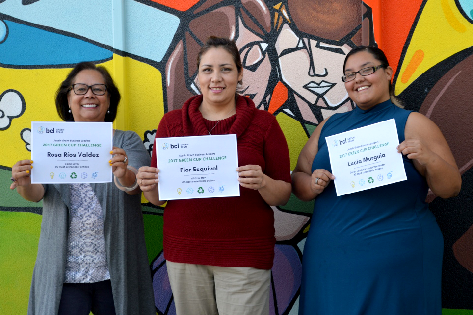Rosa and two other BCL employees showing off their Green Cup certificates. Colorful mural in background.