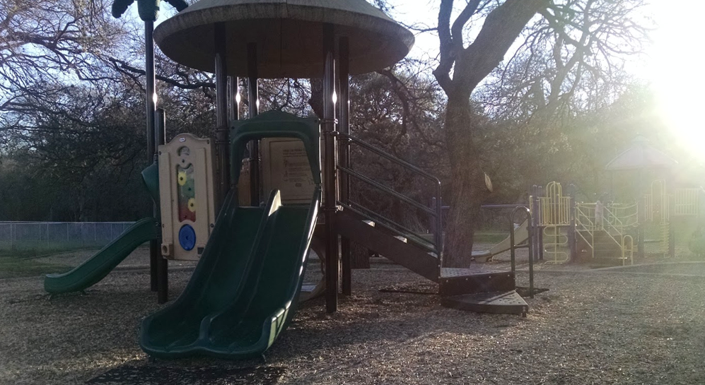 Playscape at dawn with sun coming up behind the trees. A slide is in the foreground.