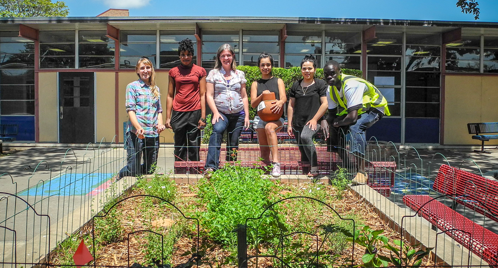 Eastside memorial students with City staff pose behind a garden on campus.