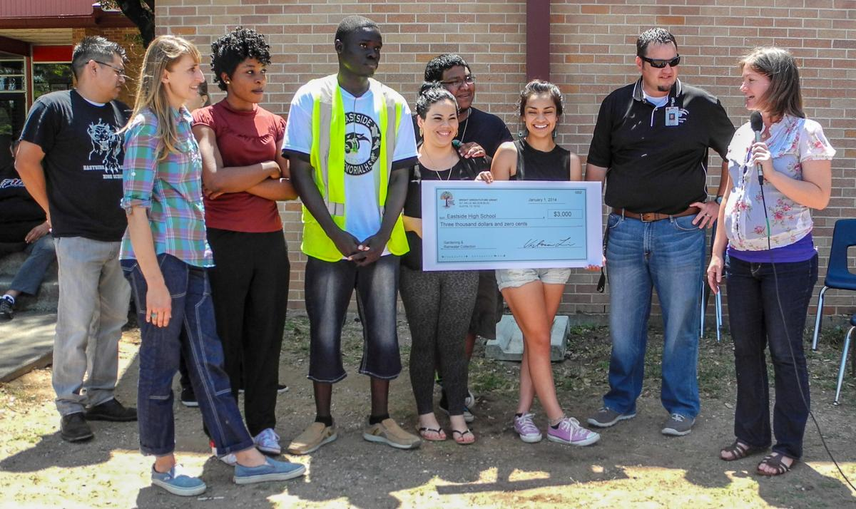 Students being presented with a big check for the project at their school.