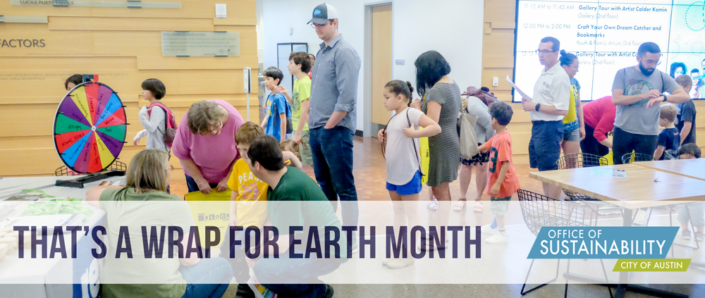 "Photo of lots of people and kids lined up to spin a wheel at an outreach table. Overlay text reads ""That's a wrap for Earth Month"""