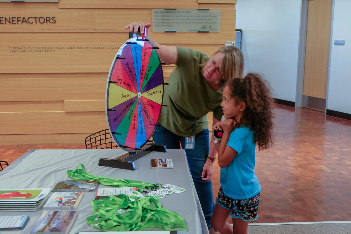 Mary Priddy showing a little kid how to spin a prize wheel.