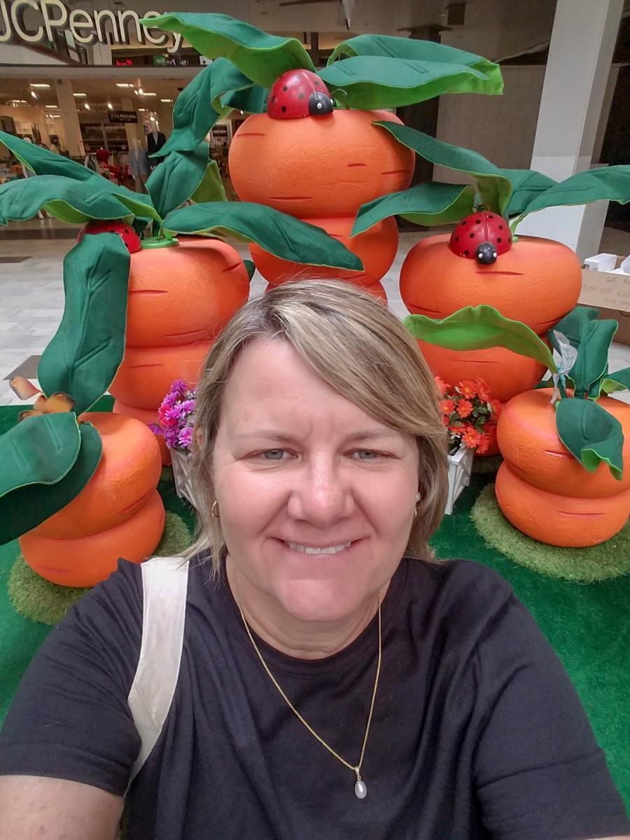 Mary taking a selfie in front of large orange carrots with lady bugs on them with JC Penny in the background.