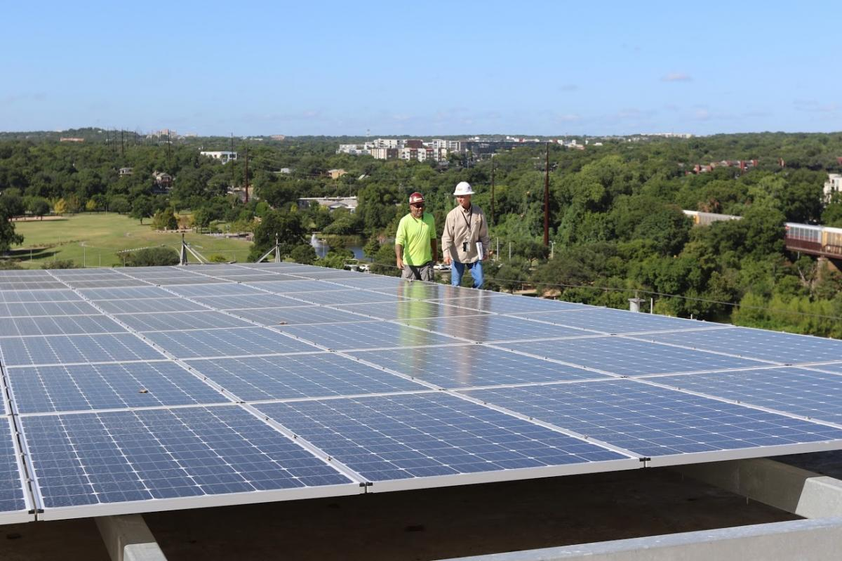 Two workers behind solar panels with trees in background