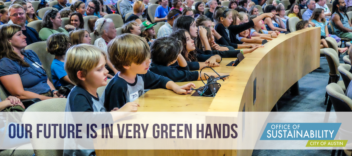 "Text reads ""Our future is in very green hands"" overlay on photo of kids sitting at long wooden desk in Austin City Council Chambers"