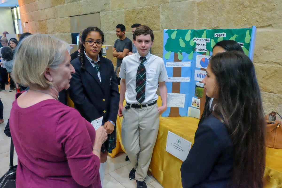 Students speaking to an adult about their sustainable projects.