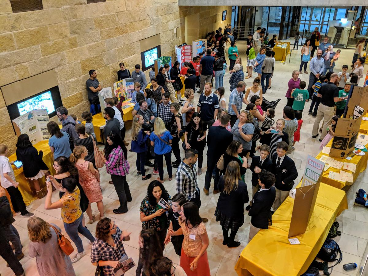 Photo taken from above in Austin CIty Hall. The atrium is full and buzzing with students and adults.