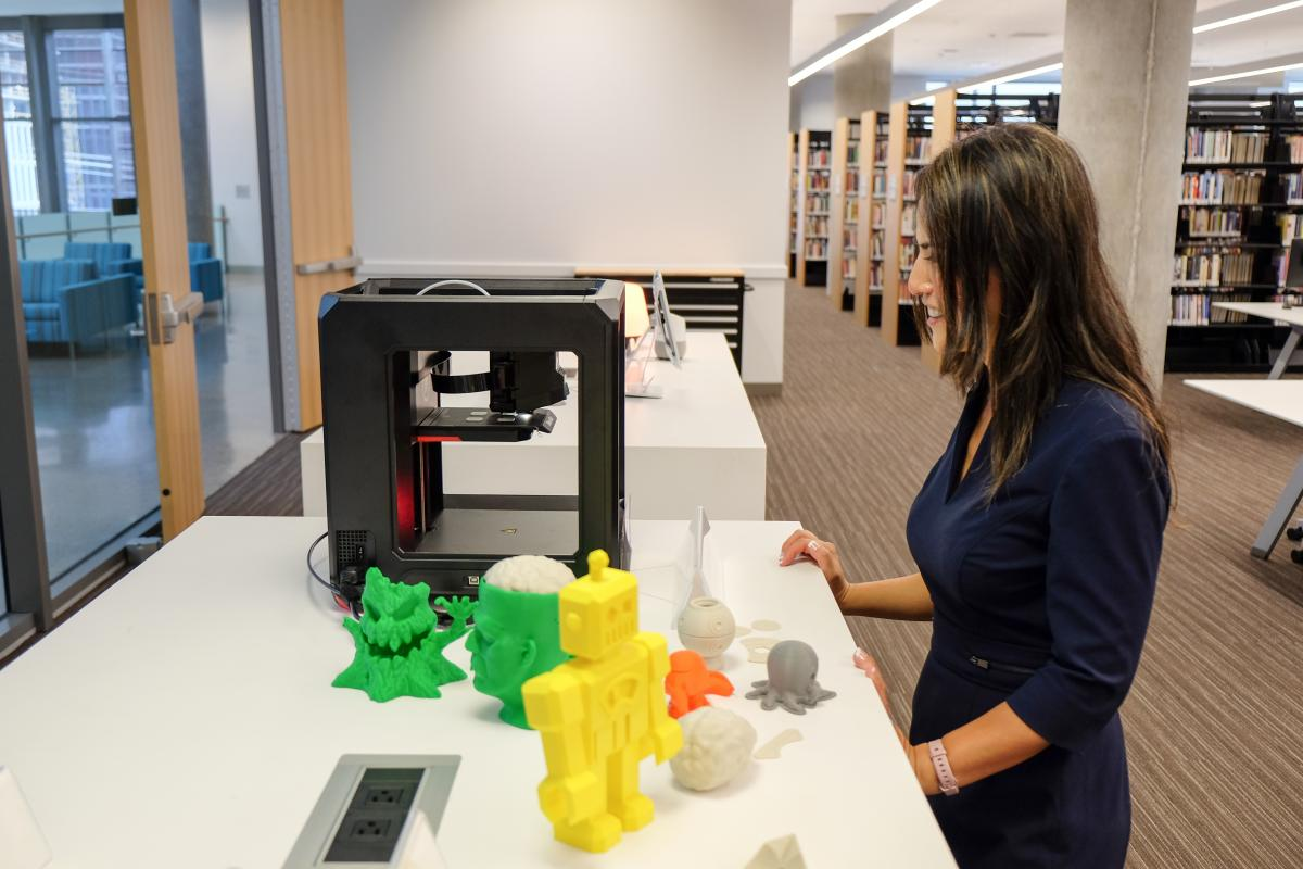 Heidi looking at the library's 3D printer and some creations that others have made.
