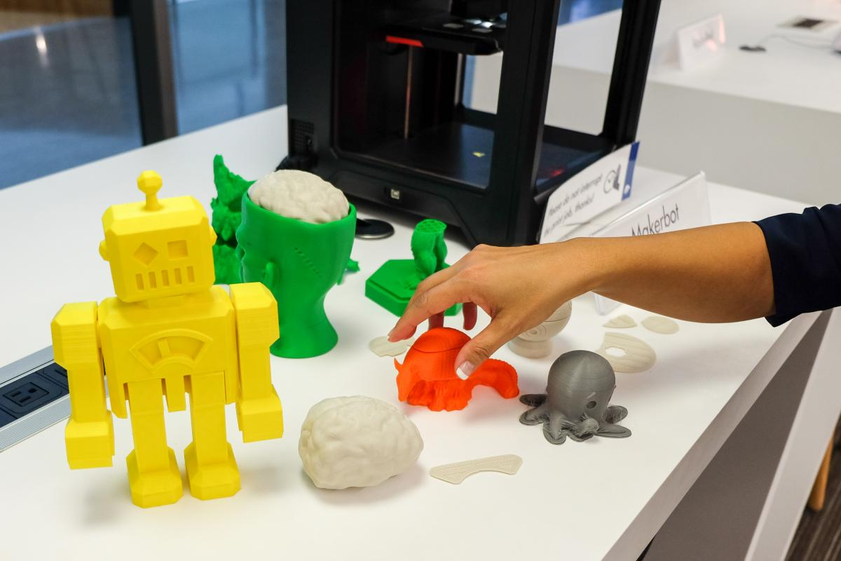Close up of 3d printer creations, including a yellow robot, green head with a brain, orange armadillo, and grey octopus.