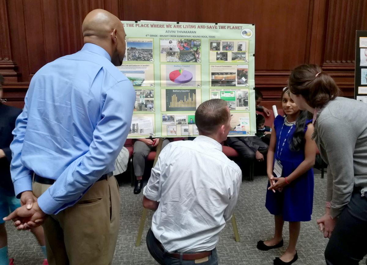 Asvini showing her project to officials on a project board.