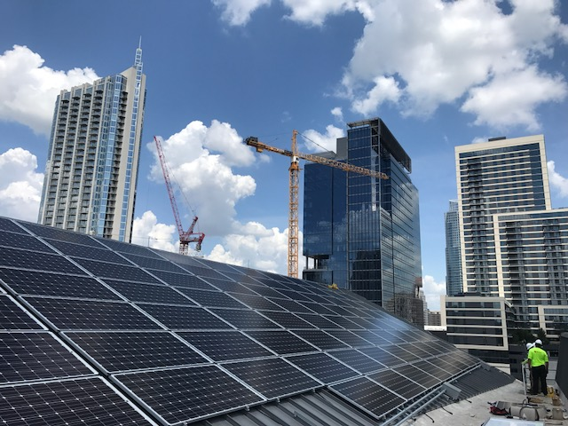 Solar panels with Austin high rise buildings in background.