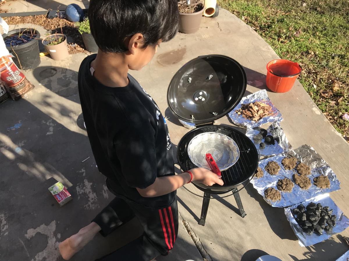 Pranav kneeling over fire pit with his materials for the experiment.