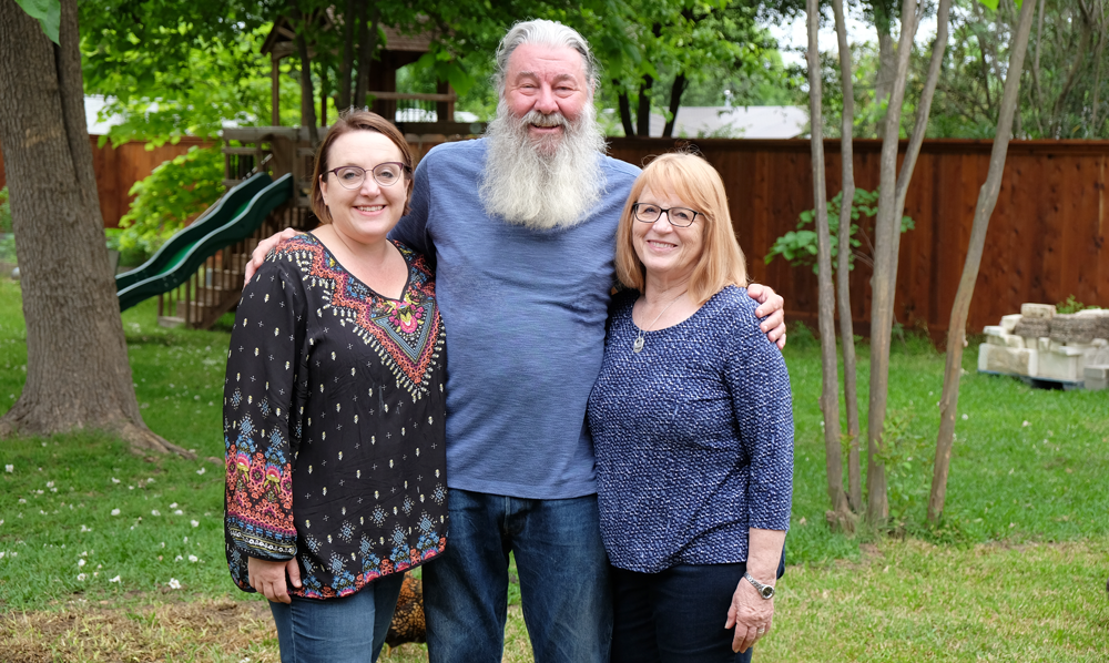 Photo with Jerry, Lauree, and Amy Bramwell standing in front of green grass, trees, and a playscape.