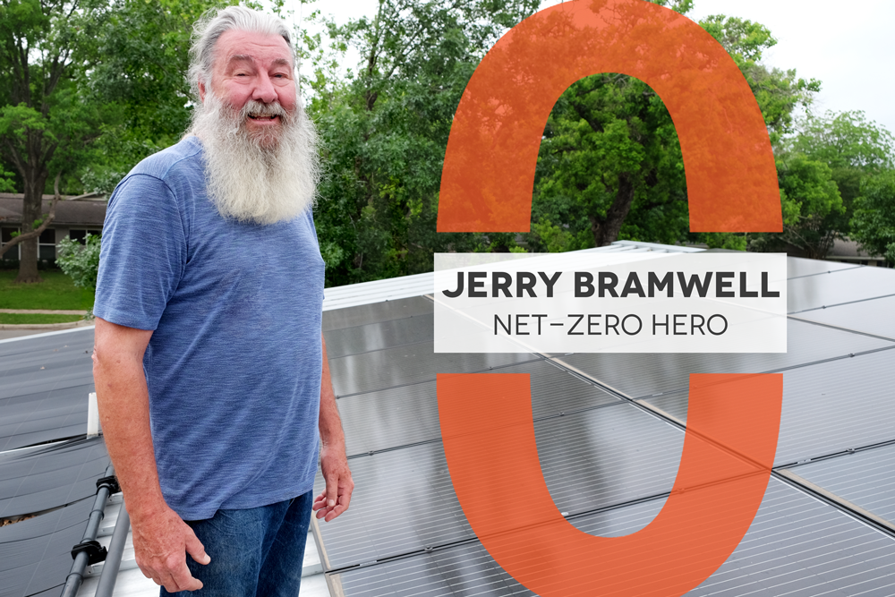 "Photo of a man with a long beard wearing a blue t-shirt standing on a roof with solar panels. There is a graphic overlay that reads ""Jerry Bramwell Net-Zero Hero"""
