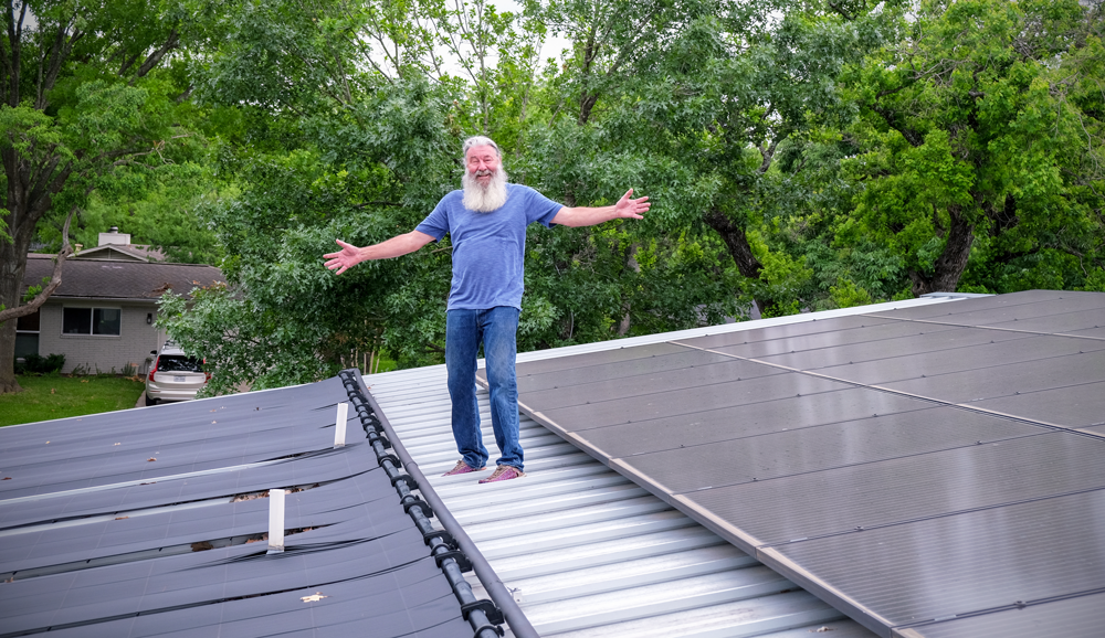 Jerry with his arms outstretched standing on top of a roof. There is a solar heating system installed on his left and a solar energy system on his right.