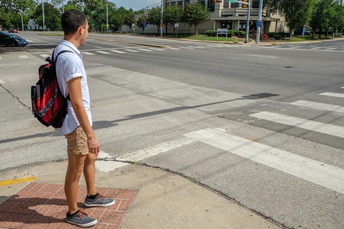 Juan waiting to cross an intersection.