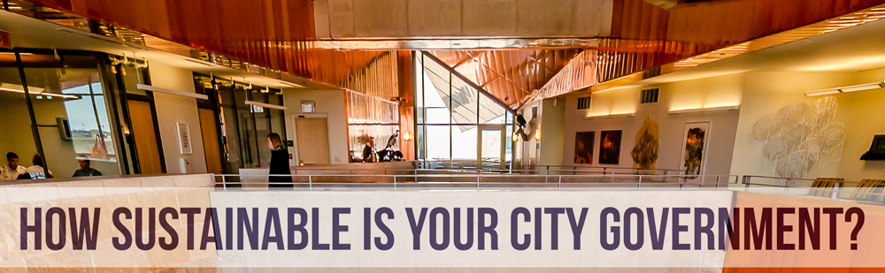 Text overlay: How sustainable is your city government? Photo background: City hall interior, gold and copper tones.
