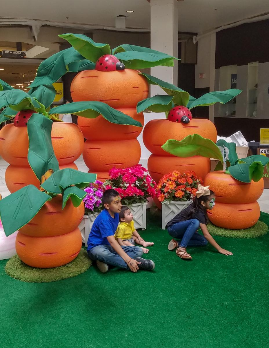 Kids taking a picture in front of large orange carrots.
