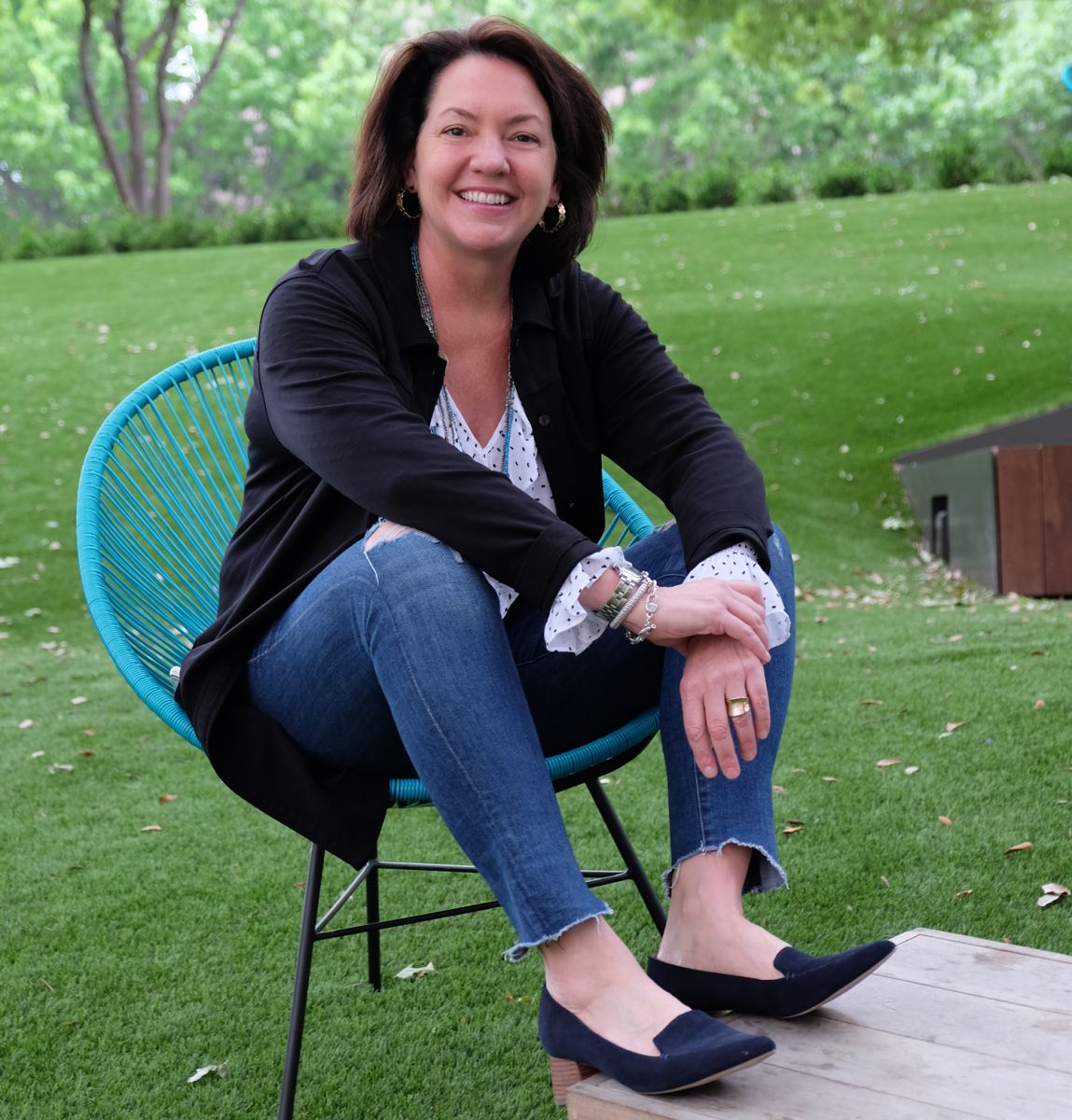 Laura Huffman seated in a teal blue chair with green grass behind her.