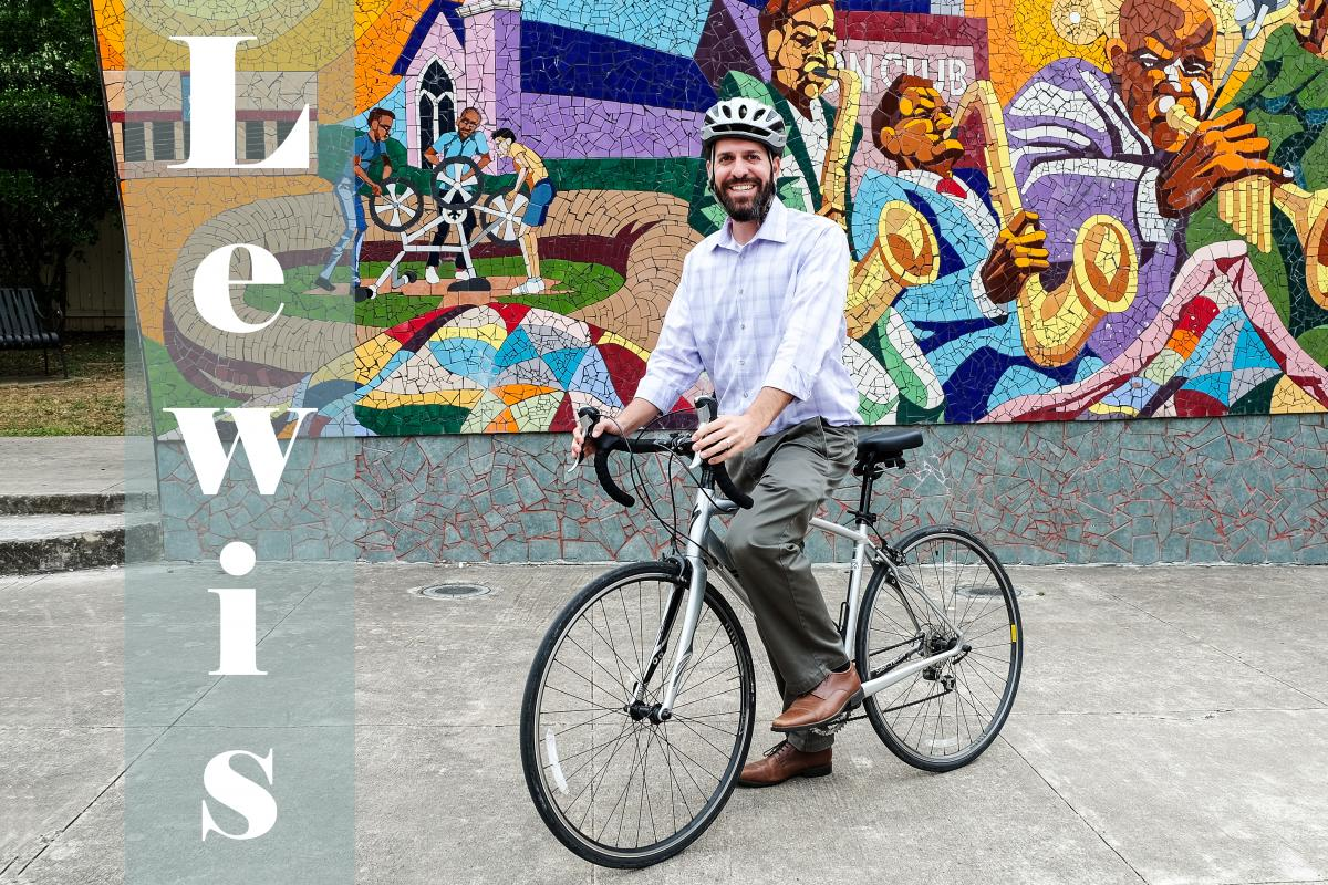 Text: Lewis, picture of Lewis on a bike with colorful mural in background