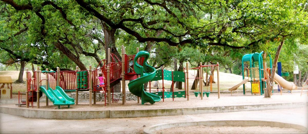 Large playscape among big oak trees with green twisty slide in the middle and a swing set.