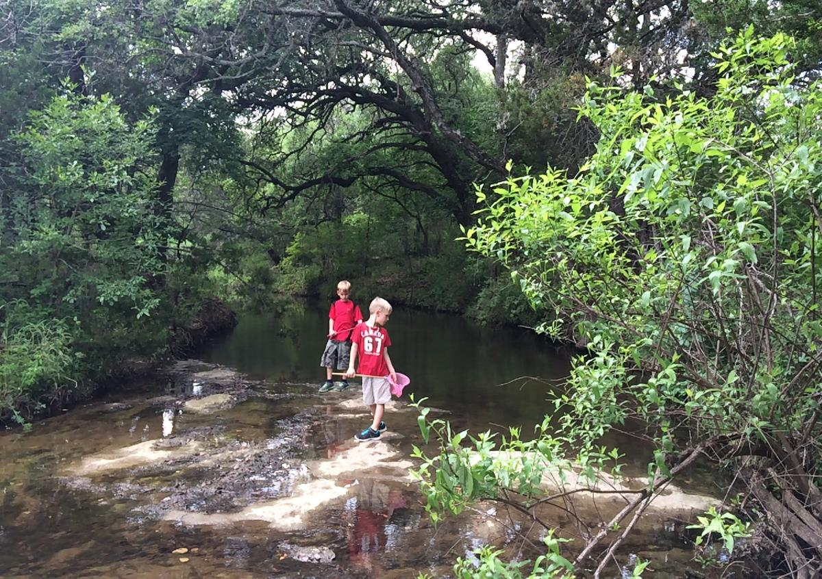 Two children playing in a river.