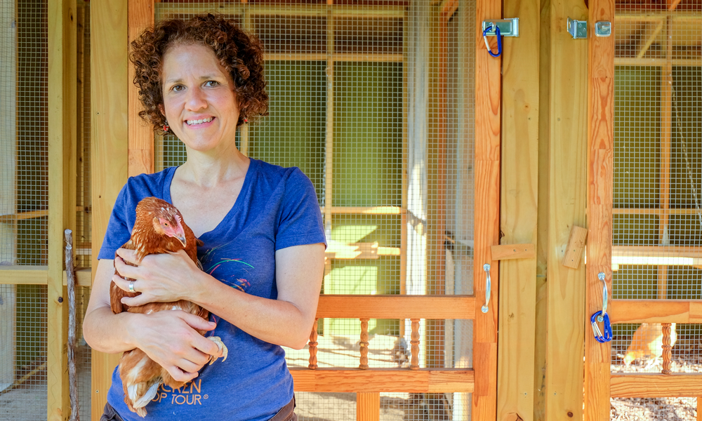 Michelle holding chicken in front of chicken coop.