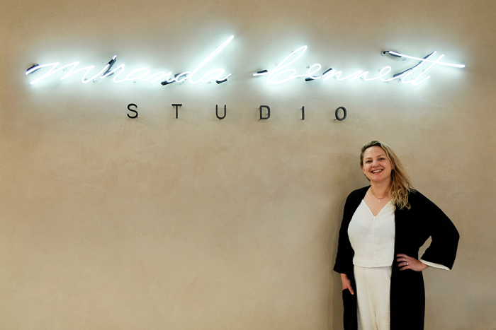 "Photo of Miranda below a neon sign that reads ""Miranda Bennett Studio"""