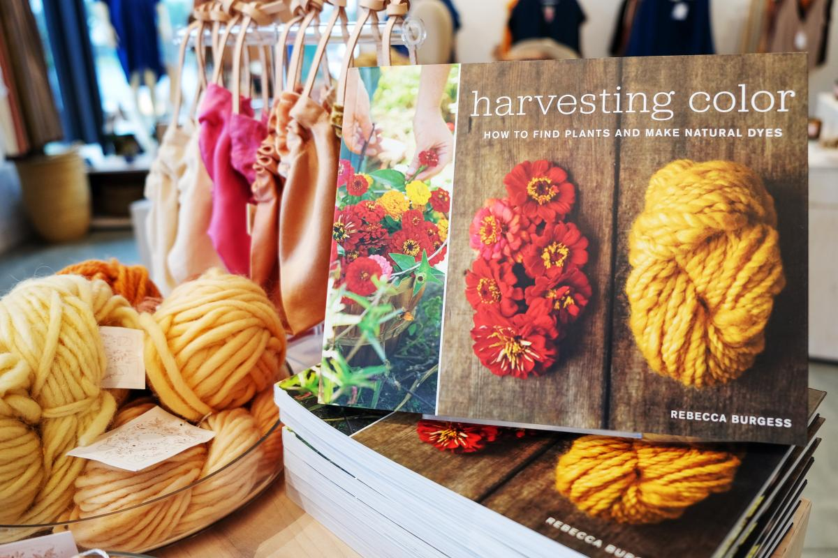 "Book titled ""Harvesting color"" with colorful bags and yarn."