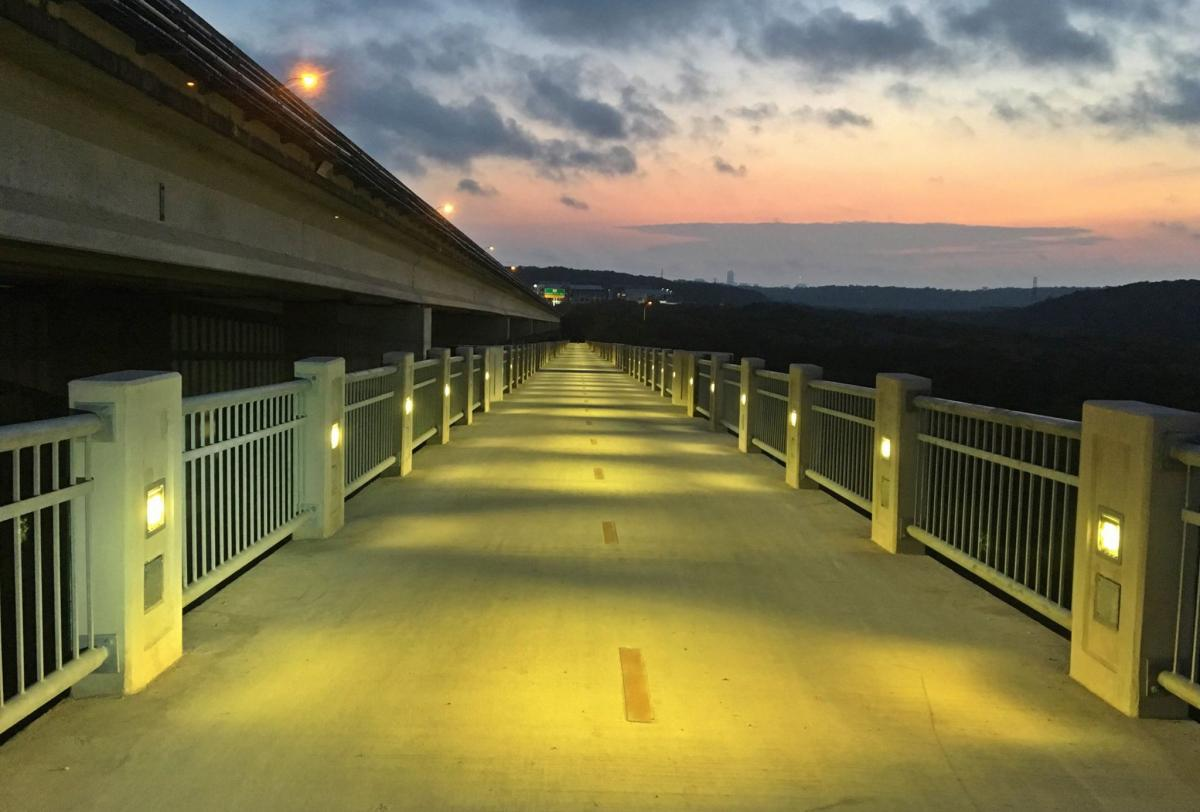 Lit pedestrian bridge at sunrise.