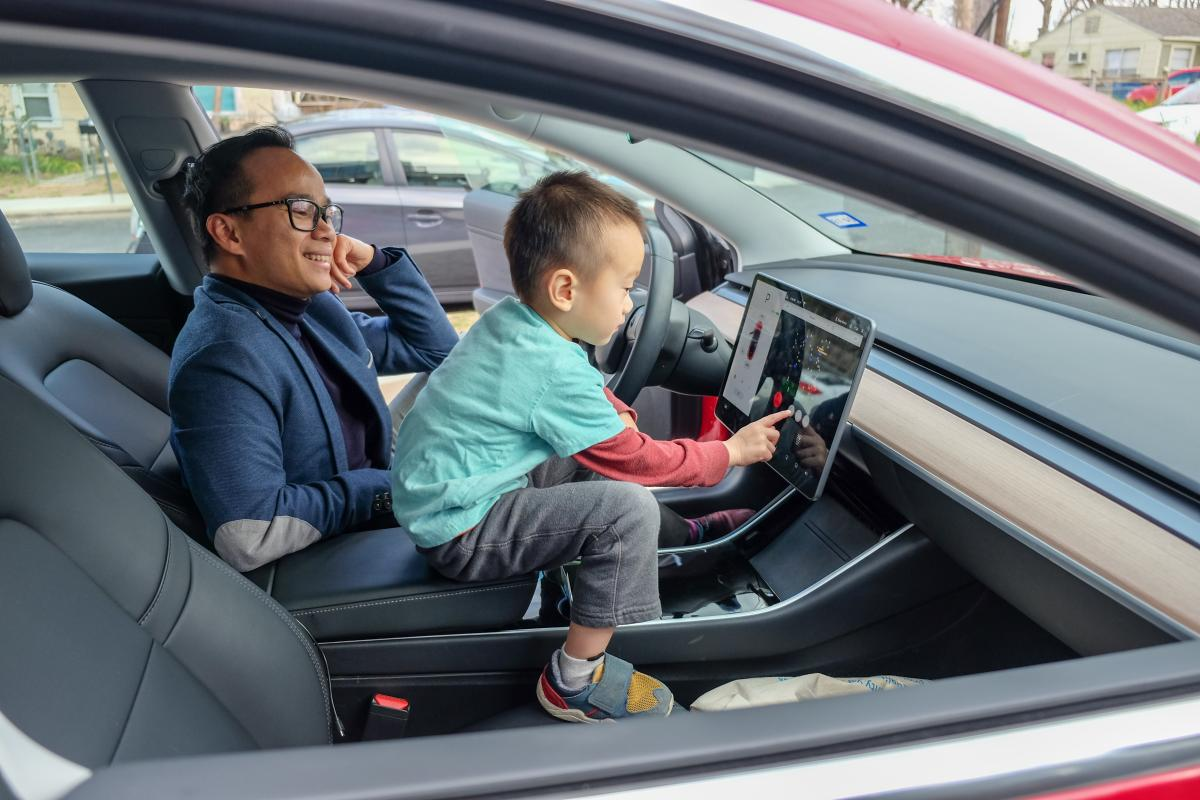 Nhat and his older son in the Tesla. His son is playing a game on the screen.