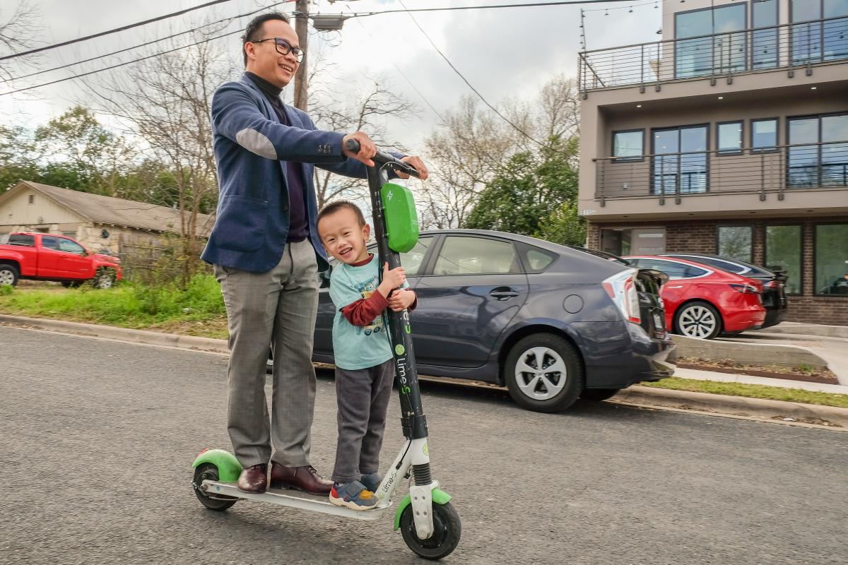 Nhat and his son riding on a scooter.