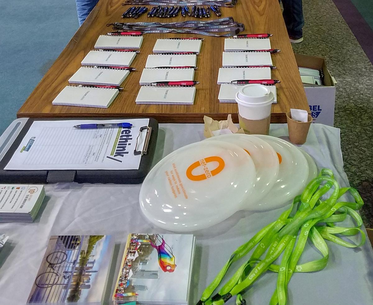 Close-up of outreach materials on a table. Glow in the dark frisbees are on the table as well as lime green lanyards.