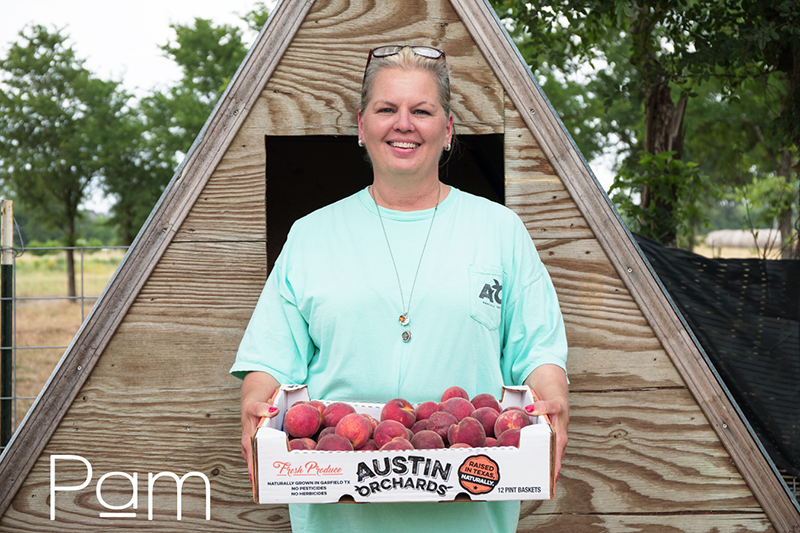 Pam holding a box of peaches standing in front of a small triangular shed or chicken coop.