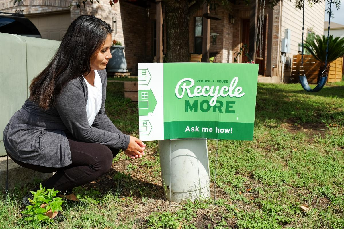 "Paula in yard with sign that reads ""Recycle More: ask me how!"""