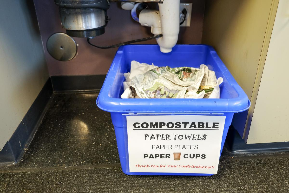 "Office compost bin with sign that reads ""Compostable: paper towels, paper plates, paper cups"""