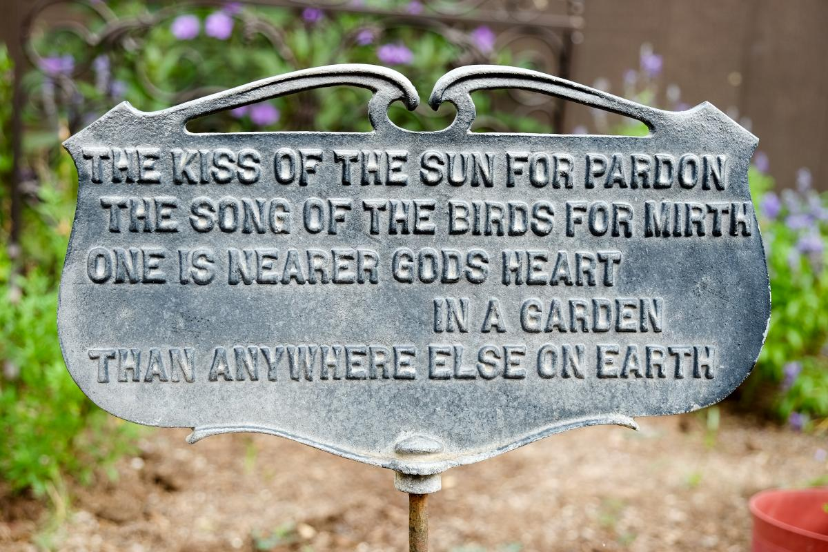 Garden sign reads: The kiss of the sun for pardon. the song of the birds for mirth, one is nearer gods heart in a garden, than anywhere else on earth.