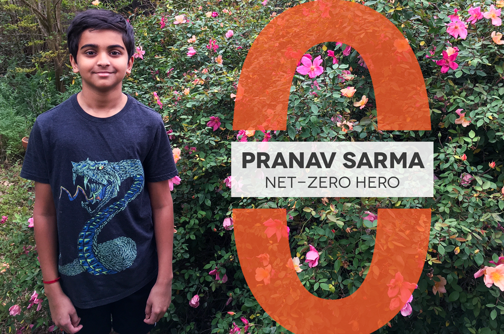 "Young boy wearing a shirt with a dragon on it stands in front of a large rose bush. A graphic next to him reads ""Pranav Sarma Net-Zero Hero"""