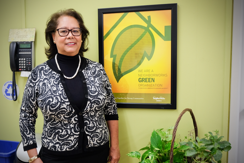 Rosa pictured in front of BCL's recycling and composting station in their break room.