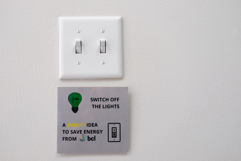 "Light switch with sign saying ""Switch off the lights. A bright idea to save energy from BCL"""