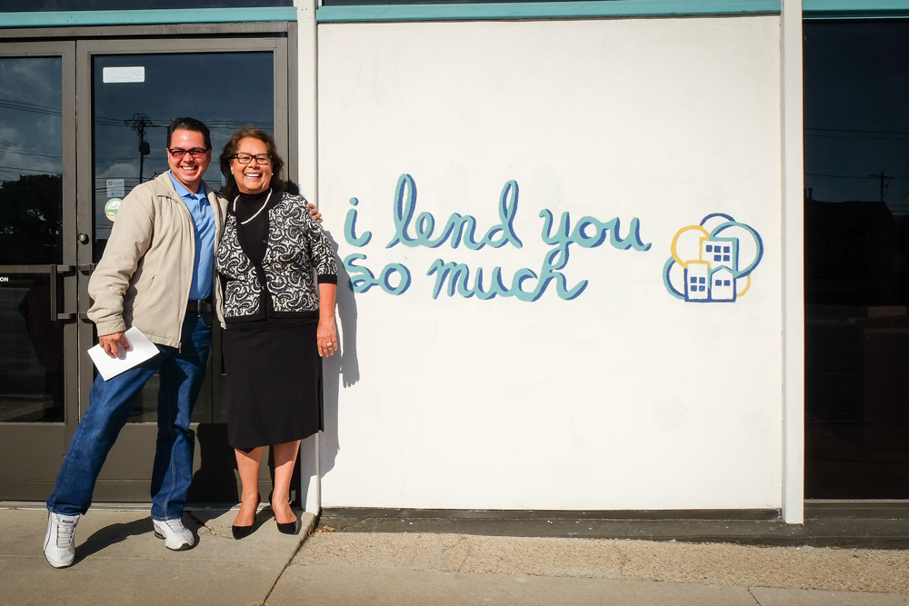 """Rosa posing with customer outside BCL. Mural reads """"I lend you so much"""""""
