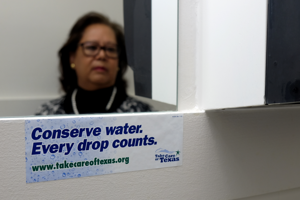 "Rosa's reflection in a mirror, sticker in front reads ""Conserve water, every drop counts"""