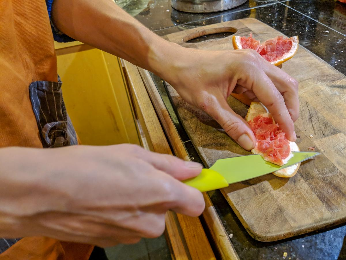 Cutting the peel from a grapefruit with a bright yellow knife.