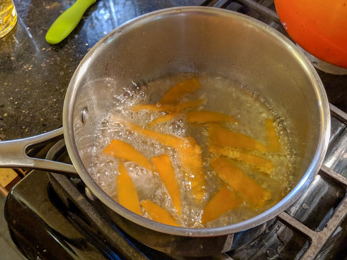 Citrus peels boiling in a pot on the stove.