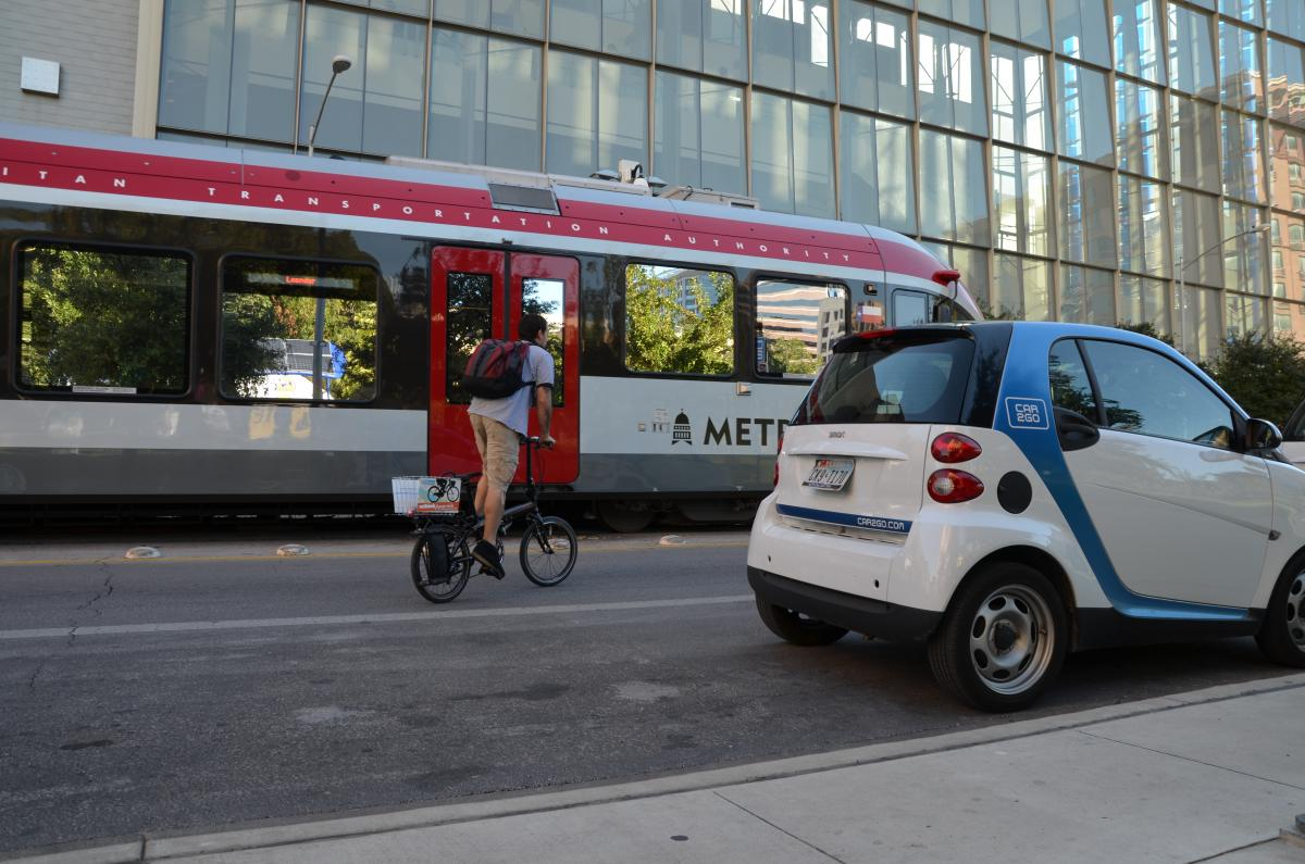 image of a person riding a bike by a bus and a car to go