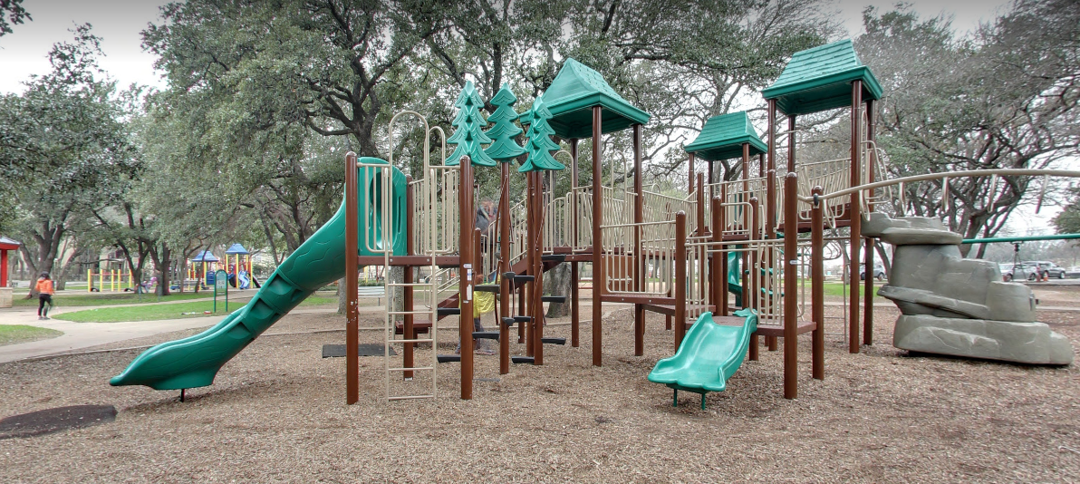 Green playscape with oak trees surrounding it, another yellow playscape is in the background.