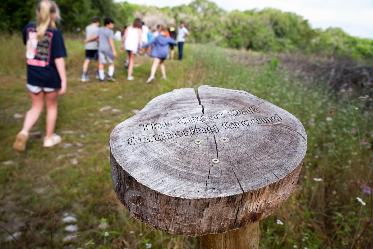 "Photo of a sign made from a tree ring that says ""The great oak gathering ground"". Kids are seen walking on the trail in the background."