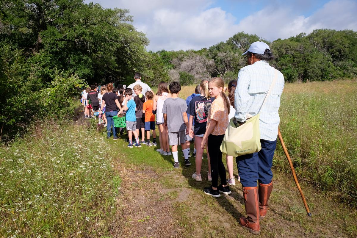 Students and teacher walking on a trail in nature.