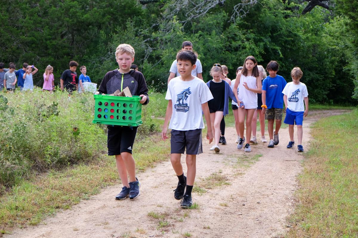 Kids walking along a trail in nature. One of them is holding a green container.